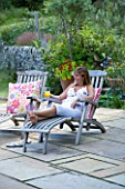CLARE MATTHEWS GARDEN  DEVON. CLARE RELAXES WITH A DRINK IN A STEAMER CHAIR ON THE PATIO. A PLACE TO SIT  DECKCHAIR  RELAX  FUN