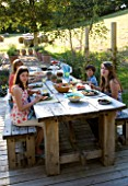 CLARE MATTHEWS GARDEN  DEVON. CLARE AND FAMILY SIT DOWN TO AN AL FRESCO LUNCH AT THE TABLE. OUTDOOR DINING. FOOD  A PLACE TO SIT  EATING