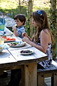 DESIGNER CLARE MATTHEWS: DEVON GARDEN. OUTDOOR SEATING AREA. WOODEN TABLE AND BENCHES ON PATIO. CHILDREN EATING LUNCH