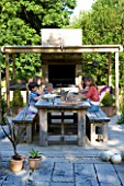 CLARE MATTHEWS GARDEN  DEVON. CLARE AND FAMILY SIT DOWN TO AN AL FRESCO LUNCH AT THE OUTDOOR DINING TABLE. PERGOLA  OUTDOOR OVEN. DINING.  DESIGNER CLARE MATTHEWS