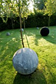 DAVID HARBER SUNDIALS: SPHERICAL STONE SCULPTURES ON LAWN WITH BLACK PEBBLED SCULPTURE DARK PLANET ON RIGHT