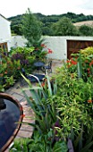 DARREN CLEMENTS GARDEN  STAFFORDSHIRE: COURTYARD GARDEN WITH MIXTURE OF ARCHITECTURAL EVERGREEN SHRUBS. BLACK TABLE AND CHAIRS AND HOT TUB