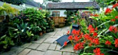 DARREN CLEMENTS GARDEN  STAFFORDSHIRE: COURTYARD WITH HOT TUB  SUNLOUNGER AND CROCOSMIA LUCIFER