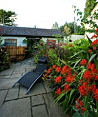 DARREN CLEMENTS GARDEN  STAFFORDSHIRE: BLACK SUN LOUNGER IN COURTYARD WITH CROCOSMIA LUCIFER  COTINUS GRACE AND HOT TUB IN BACKGROUND