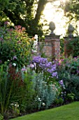 WILKINS PLECK  STAFFORDSHIRE: HERBACEOUS BORDER BESIDE A BRICK PILLARED WALL: EUPATORIUM  PHLOX DIERAMA PULCHERRIMUM  LOBELIA AND ARTEMISIA