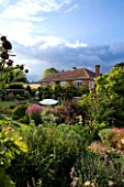 MARINERS GARDEN  BERKSHIRE. DESIGNER FENJA ANDERSON - THE HOUSE FROM THE UPPER GARDEN WITH STORMY SKY. MAGNOLIA X LOEBNERI LEONARD MESSEL  PHYSOCARPUS DIABOLO  CYNARA CARDUNCULUS