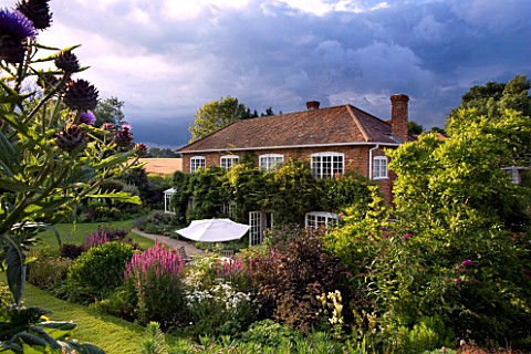 MARINERS_GARDEN__BERKSHIRE_DESIGNER_FENJA_ANDERSON__THE_HOUSE_FROM_THE_UPPER_GARDEN_WITH_STORMY_SKY_