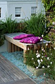 ROOF GARDEN  HOLLAND PARK  LONDON. DESIGNER: CHARLOTTE ROWE. WOODEN BENCH  MAUVE CUSHIONS ON DECKED TERRACE WITH PALE BLUE GLASS GRAVEL AND GAURA LINDHEIMERI WHIRLING BUTTERFLIES