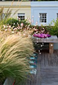 ROOF GARDEN  HOLLAND PARK  LONDON. DESIGNER: CHARLOTTE ROWE. WOODEN BENCH MAUVE CUSHION  IP DECK TERRACE  LED LIGHTING  STIPA TENUISSIMA  GAURA LINDHEIMERI WHIRLING BUTTERFLIES