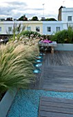 ROOF GARDEN  HOLLAND PARK  LONDON. DESIGNER: CHARLOTTE ROWE. WOODEN BENCH MAUVE CUSHION  IPE DECK TERRACE  LED LIGHTING  STIPA TENUISSIMA  GAURA LINDHEIMERI WHIRLING BUTTERFLIES