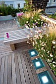 ROOF GARDEN  HOLLAND PARK  LONDON. DESIGNER: CHARLOTTE ROWE.WOODEN BENCH  CANDLES  IPE DECKED TERRACE  WHITE LED LIGHTING  RAISED BEDS WITH GAURA LINDHEIMERI WHIRLING BUTTERFLIES