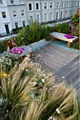 ROOF GARDEN HOLLAND PARK LONDON.DESIGNER CHARLOTTE ROWE.DECKED TERRACE WOODEN BENCHES PINK CUSHIONS BLUE GLASS GRAVEL  GAURA LINDHEIMERI WHIRLING BUTTERFLIES  STIPA TENUISSIMA