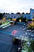 ROOF GARDEN  HOLLAND PARK  LONDON. DESIGNER: CHARLOTTE ROWE. DECKED TERRACE IN EVENING WITH LED LIGHTING  CANDLES ON WOODEN BENCH  STIPA TENUISSIMA  GAURA LINDHEIMERI