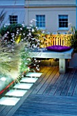 ROOF GARDEN  HOLLAND PARK  LONDON. DESIGNER: CHARLOTTE ROWE. DECKED TERRACE AT NIGHT WITH LED LIGHTING  STIPA TENUISSIMA  GAURA LINDHEIMERI WHIRLING BUTTERFLIES
