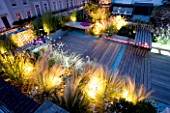 ROOF GARDEN  HOLLAND PARK  LONDON. DESIGNER: CHARLOTTE ROWE. DECKED TERRACE AT NIGHT WITH LED LIGHTING AND BLUE GLASS GRAVEL  STIPA TENUISSIMA  GAURA LINDHEIMERI