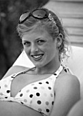 GIRL (AGED 15) SMILING IN A DECKCHAIR. SUNGLASSES. BLACK AND WHITE IMAGE