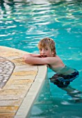 BOY (AGED 13) LEANING ON THE EDGE OF A SWIMMING POOL