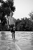 BOY (AGED 13) JUMPING INTO A SWIMMING POOL. WALKING ON WATER. BLACK AND WHITE IMAGE