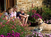 RICKYARD BARN GARDEN  NORTHAMPTONSHIRE: JANE NICHOLS SITTING ON THE STEPS WITH ROBERT AND HAZEL. MURPHY THE DOG LYING ON THE GRAVEL