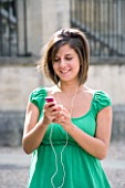 TEENAGE GIRL (16-17 YEARS) IN JEAN MINISKIRT AND GREEN TOP LISTENING TO MP3 PLAYER. TEENAGE GIRLS  ONE TEENAGE GIRL ONLY  IPOD  MUSIC  CASUAL CLOTHING  WAIST UP  SMILING  HAPPY