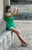 TEENAGE GIRL (16-17 YEARS) IN JEAN MINISKIRT AND GREEN TOP TAKING PHOTOGRAPH. DIGITAL CAMERA  TEENAGE GIRLS  ONE TEENAGE GIRL ONLY  CASUAL CLOTHING  PHOTOGRAPHY  FULL LENGTH