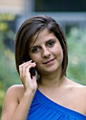 TEENAGE GIRL (16-17 YEARS) IN BLUE TOP TALKING ON MOBILE PHONE  SMILING  TEENAGE GIRLS  ONE TEENAGE GIRL ONLY  CASUAL CLOTHING  HAPPY  HAPPINESS  STUDENT  COLLEGE  ON THE PHONE