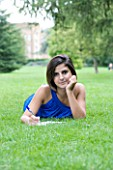 TEENAGE GIRL (16-17 YEARS) IN BLUE TOP LYING ON GRASS WRITING. SMILING  TEENAGE GIRLS  ONE TEENAGE GIRL ONLY  CASUAL CLOTHING  HAPPY  HAPPINESS  STUDENT  COLLEGE  IN THE PARK