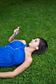 TEENAGE GIRL (16-17 YEARS) IN BLUE TOP LYING ON GRASS WRITING LISTENING TO MP3 PLAYER. MUSIC  TEENAGE GIRLS  ONE TEENAGE GIRL ONLY  CASUAL CLOTHING  STUDENT  COLLEGE  IN THE PARK