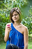 TEENAGE GIRL (16-17 YEARS) IN BLUE TOP SITTING LISTENING TO MP3 PLAYER. MUSIC  TEENAGE GIRLS  ONE TEENAGE GIRL ONLY  CASUAL CLOTHING  STUDENT  COLLEGE  MUSIC