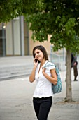 TEENAGE GIRL (16-17 YEARS) IN WHITE SHIRT TALKING ON MOBILE PHONE  BAG OVER SHOULDER. TEENAGE GIRLS  ONE TEENAGE GIRL ONLY  STUDENT  COLLEGE  SMILE  SMILING  HAPPY  CASUAL CLOTHING