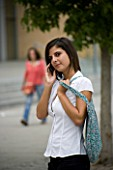 TEENAGE GIRL (16-17 YEARS) IN WHITE SHIRT AND BLACK TROUSERS TALKING ON MOBILE PHONE  BAG OVER SHOULDER. TEENAGE GIRLS  ONE TEENAGE GIRL ONLY  STUDENT  COLLEGE  CASUAL CLOTHING