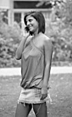 BLACK AND WHITE IMAGE. TEENAGE GIRL (16-17 YEARS) IN A PARK OUTSIDE COLLEGE TALKING ON THE PHONE. TEENAGE GIRLS  ONE TEENAGE GIRL ONLY  STUDENT  COLLEGE  CASUAL CLOTHING
