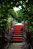 THROUGHAM COURT  GLOUCESTERSHIRE. DESIGNER: CHRISTINE FACER: THE ROYAL STEPS - RED CARPET UP STEPS WITH PHORMIUMS AND PLEACHED LIME WALK BEYOND