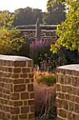 RICKYARD BARN GARDEN  NORTHAMPTONSHIRE - VIEW THROUGH STONE WALL INTO GRAVEL GARDEN IN SEPTEMBER WITH STIPA ARUNDINACEA  VERBENA BONARIENSIS AND DRIFTWOOD SCULPTURE