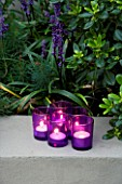 DESIGNER - CHARLOTTE ROWE  LONDON: CHARLOTTE ROWES OWN GARDEN AT NIGHT -  TEA LIGHTS (CANDLES) INSIDE PURPLE GLASS CONTAINERS BESIDE LIRIOPE MUSCARI