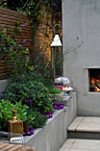 DESIGNER - CHARLOTTE ROWE  LONDON: CHARLOTTE ROWES OWN GARDEN AT NIGHT - RENDERED RAISED BED BESIDE FIREPLACE WITH LIRIOPE MUSCARI  MOROCCAN CANDLE HOLDER  CANDLES