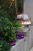 DESIGNER - CHARLOTTE ROWE  LONDON: CHARLOTTE ROWES OWN GARDEN AT NIGHT - RENDERED RAISED BED BESIDE FIREPLACE WITH LIRIOPE MUSCARI  CANDLES AND A LARGE GLASS BOWL WITH GERBERAS