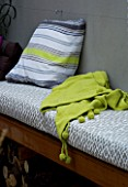 DESIGNER - CHARLOTTE ROWE  LONDON: CHARLOTTE ROWES OWN GARDEN AT NIGHT - WESTERN RED CEDAR SEAT WITH CUSHIONS AND LIME GREEN THROW