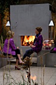 DESIGNER - CHARLOTTE ROWE  LONDON: CHARLOTTE ROWES OWN GARDEN AT NIGHT - CHARLOTTE SITS CHATTING WITH ONE OF HER FRIENDS BESIDE THE OUTDOOR FIREPLACE
