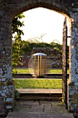 DAVID HARBER SUNDIALS: VIEW THROUGH A GATE AND ARCHWAY TO ETHER WATER FEATURE IN A POOL IN EARLY MORNING DAWN LIGHT WITH CHAMOMILE LAWN