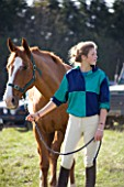 GIRL (AGED 15) AT HORSE JUMPING COMPETITION WITH HORSE