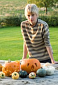 HALLOWEEN: BOY (AGED 13) ADMIRES A STILL LIFE ON OUTDOOR WOODEN TABLE WITH PUMPKINS  SQUASHES AND GOUR