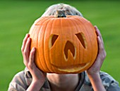 HALLOWEEN: BOY (AGED 13) WITH PUMPKIN IN FRONT OF FACE