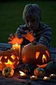 HALLOWEEN: BOY (AGED 13) PUTS HANDS UP TO CANDLE LIGHT - STILL LIFE ON WOODEN TABLE AT NIGHT WITH CANDLES  PUMPKINS  SQUASHES AND GOURDS