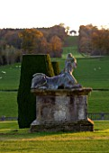 CASTLE HILL  DEVON: STATUE ON PEDESTAL ON THE TERRACES WITH VIEW TO THE TRIUMPHAL ARCH IN AUTUMN. EVENING LIGHT