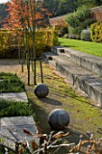 MARKS HALL  ESSEX : THE GARDEN OF SPHERES IN THE WALLED GARDEN: STONE BALLS  STONE STEPS AND AMELANCHIER X GRANDIFLORA ROBIN HILL