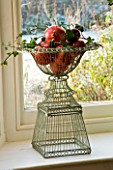 BOONSHILL FARM AT CHRISTMAS: WINDOW DECORATION - ORNATE METAL WIRE CONTAINERS WITH APPLES  IVY AND POMEGRANATES. DESIGNER: LISETTE PLEASANCE