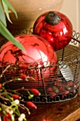 BOONSHILL FARM AT CHRISTMAS: DECORATIVE RED CHRISTMAS TREE BAUBLES IN A WIRE BASKET. DESIGNER: LISETTE PLEASANCE