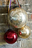 BOONSHILL FARM AT CHRISTMAS: THE LIVING ROOM - DECORATIVE CHRISTMAS BAUBLES ON THE FIREPLACE. DESIGNER: LISETTE PLEASANCE