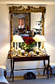 BOONSHILL FARM AT CHRISTMAS: THE LIVING ROOM - BEAUTIFUL TABLE AND MIRROR WITH POINSETTIA. DESIGNER: LISETTE PLEASANCE